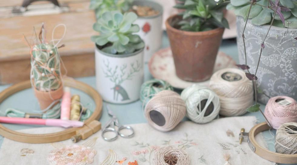 aiguille en fête - bobines de fil - plantes vertes - pots de fleurs - tissus - textiles - table bleue - jardin