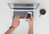aiguille en fête - réservation en ligne - ordinateur mac - mains hommes - smartphone - montre - tasse de café - blanc